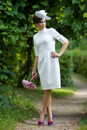 Wedding  Bride in a sheath dress standing next to a vineyard on a summer evening