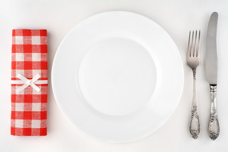 Vintage cutlery set with fork, knife, plate and red checkered napkin. Overhead view. photo