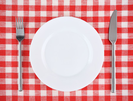 checker plate: Plate with fork and knife on a red checkered tablecloth.