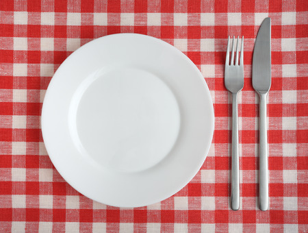 Plate with fork and knife on a red checkered tablecloth. photo