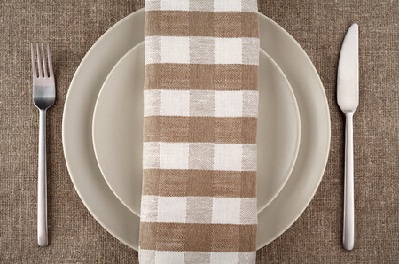 Table setting. Beige plate, fork, knife and beige linen napkin and tablecloth. photo