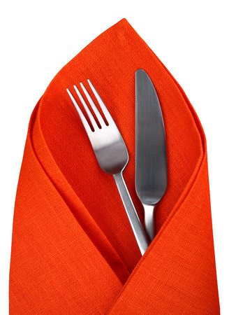 Orange napkin with knife and fork isolated. Table setting for Halloween day. photo