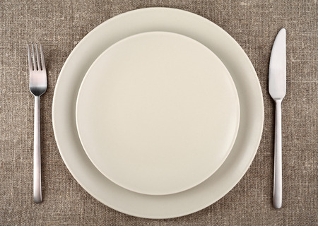 Table setting. Beige plate, fork, knife and beige linen tablecloth. photo