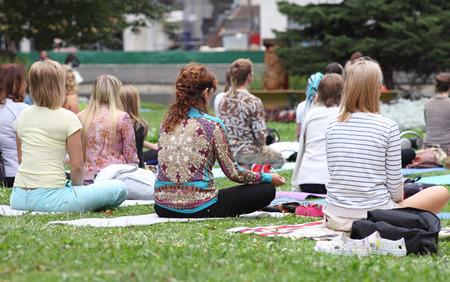 Minsk, Belarus - august 16, 2014: Yoga. People practicing yoga in park