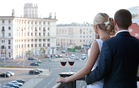 Couple on balcony with a glass of wine watching the city. photo