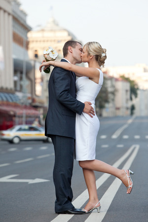 Find Similar Images Couple in a kiss on the road. Newlyweds kissing on the dividing strip. Wedding theme.