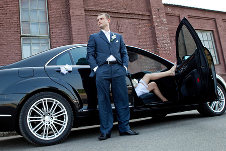 Wedding ceremony. Groom next to an executive car which sits bride. photo