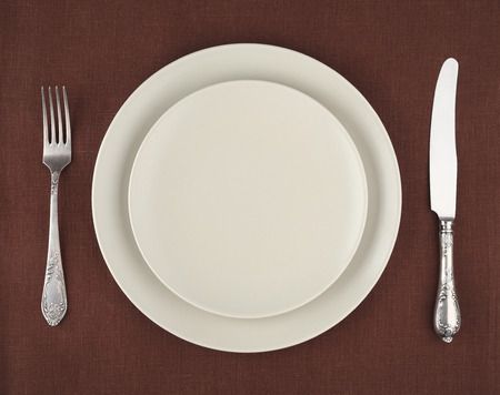 Table setting. Beige plates and vintage fork and knife on a brown linen tablecloth photo