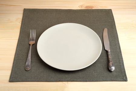 Empty plate with vintage fork and knife on green linen napkin on a wooden table photo