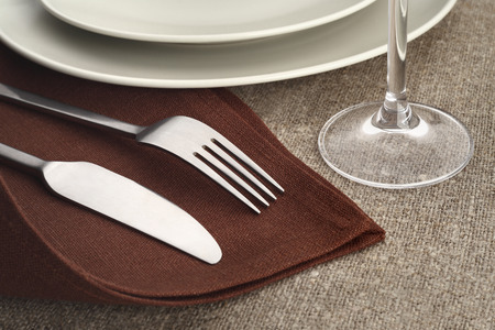 Table setting. Cutlery set with fork, knife, plate and glass on brown linen napkins and tablecloth. photo