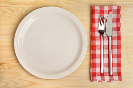 Empty plate with fork and knife on red checkered napkin on wooden background. photo