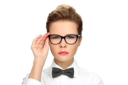 Successful business woman wearing glasses, a white shirt with a bow tie. Modern girl corrects glasses on his face.