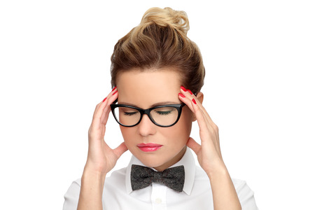 Headache migraine people. Young beautiful woman in glasses, white shirt and bow tie puts hands on the head, isolated on white. Concept - problems, fatigue, stress and headache.