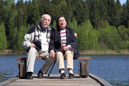 brighter: Elderly couple looking into the distance with a belief in a brighter future. Elderly couple sitting on bench near the lake.