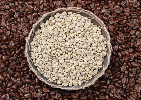 unroasted: Coffee beans. Unroasted and black roasted coffee beans as background.