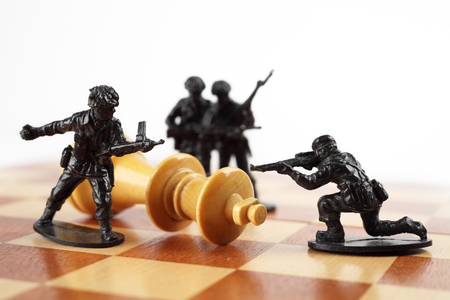 kill: War concept. Toy soldiers kill chess King. Death of king.