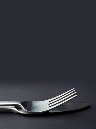 Fork and knife close up on a dark background with copy space