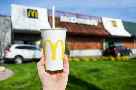 Minsk, Belarus, may 18, 2017: McDonalds soft drink paper cup in hand on blurry McDonalds Restaurant background