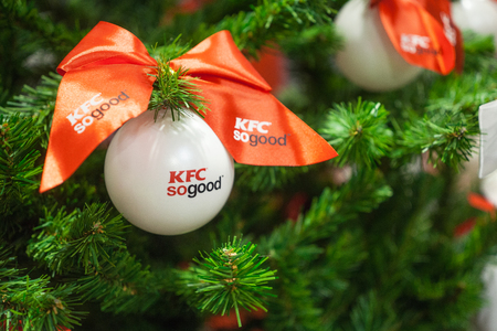 Minsk, Belarus - november 20, 2017: Closeup of white bauble with logo KFC hanging from a decorated Christmas tree