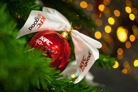 Minsk, Belarus - november 20, 2017: Closeup of red bauble with logo KFC hanging from a decorated Christmas tree