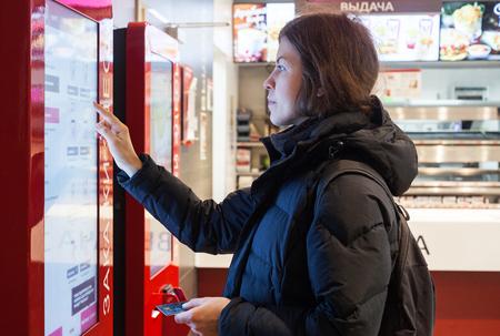 MINSK, BELARUS - november 26, 2017: Woman uses KFC kiosk to order food at KFC restaurant Redactioneel