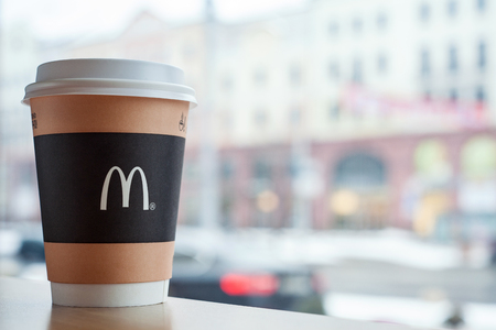 Minsk, Belarus, February 18, 2018: Paper cup of coffee with McDonald's logo on table near window on background of city in McDonald's restaurant Editorial