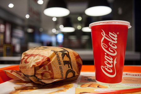 Minsk, Belarus, March 27, 2018: Sandwich with KFC logo and рaper cup with Coca-Cola logo on table in KFC Restaurant Editorial