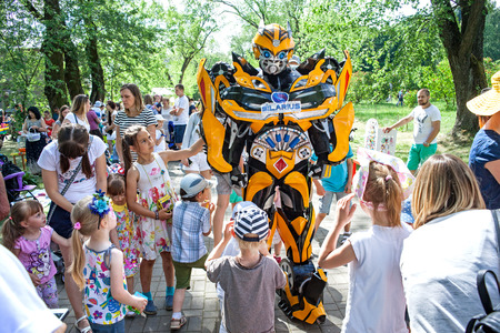Minsk, Belarus, June 3, 2018: Animator in a suit of robot transformer among children in a city park.
