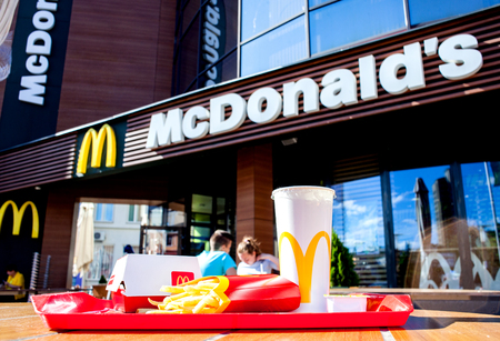 Minsk, Belarus - august 12, 2018: Tray with Big Mac hamburger menu on table on an open terrace in background of McDonald restaurant. Sajtókép