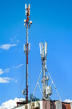 Communication antennas on a building, against blue sky. Imagens