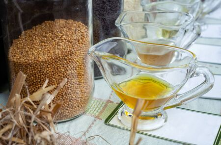 Mustard seeds in jar and oil pressed from them. Stockfoto