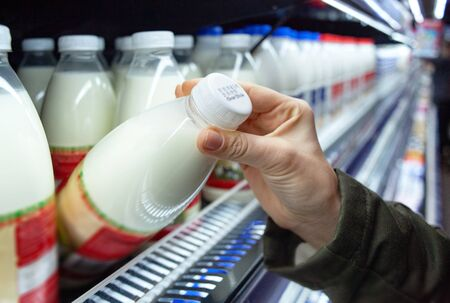Womans hand holding milk bottle in supermarket. Man shopping milk in grocery store. Man checks product expiration date before buying it. Close-up. 免版税图像