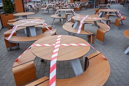 Outdoor cafe / restaurant is closed for quarantine during coronavirus epidemic. Access to restaurant, cafe is prohibited for duration of pandemic, seats are blocked with a warning tape
