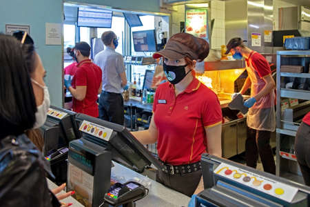 MINSK, BELARUS - April 27, 2020: Workers in medical masks serve customers at McDonald's restaurant during a Coronavirus epidemic. Lifestyle during pandemic. 新聞圖片