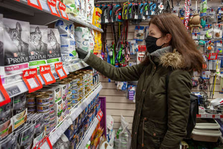 MINSK, BELARUS - April 27, 2020: Buyer wearing a protective mask. Shopping during the pandemic. Man shopping pet food in pet shop. 新聞圖片