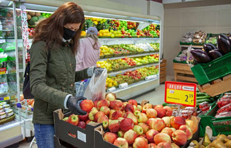 MINSK, BELARUS - April 27, 2020: Young woman wearing medical mask shopping in supermarket during coronavirus pneumonia outbreak. Protection and prevent measures while epidemic time.