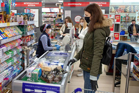 MINSK, BELARUS - April 27, 2020: Customers and grocery store workers in medical masks and gloves to protect against viruses. Protective measures during the coronavirus pandemic.