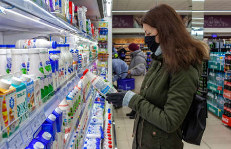MINSK, BELARUS - April 27, 2020: Man in protective mask shopping milk in grocery store during coronavirus epidemic. Young woman reading ingredients, declaration or expiration date on product.