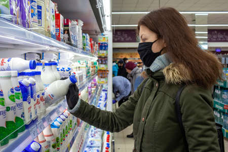 MINSK, BELARUS - April 27, 2020: Woman in a protective mask and gloves holding milk bottle in grocery store during coronavirus epidemic. Man checks product expiration date before buying it. 新聞圖片