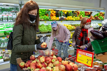 MINSK, BELARUS - April 27, 2020: Buyer in mask and protective gloves buying food in shop at coronavirus epidemic.
