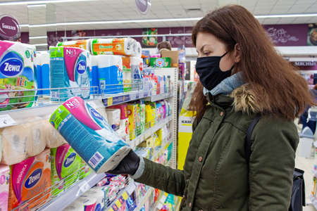MINSK, BELARUS - April 27, 2020: Buyer in a protective mask chooses toilet paper in a supermarket during a coronavirus epidemic. Shopping during a pardemic. 新聞圖片