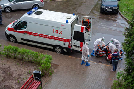MINSK, BELARUS - May 12, 2020: Team of medical personnel in protective suits hospitalizes patient during of coronavirus epidemic.