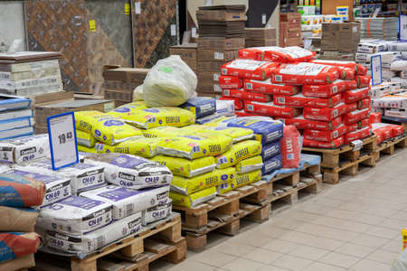 MINSK, BELARUS - May 16, 2020: Building materials are sold in a hardware store. Bags of cement, plaster and other goods for construction and repair are stacked on pallets.
