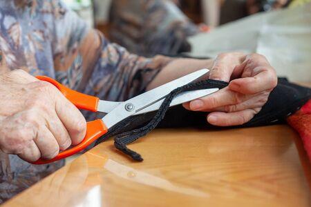 Hands of an elderly woman cut the fabric. Cutting fabric closeup. Dressmaker at work. Tailoring. 版權商用圖片