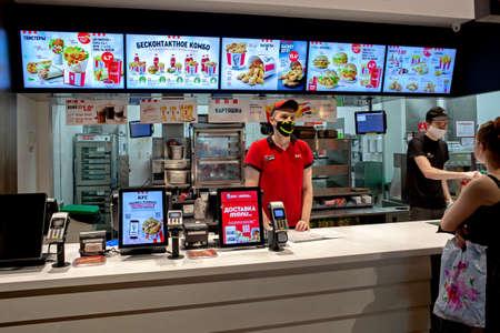 MINSK, BELARUS - June 11, 2020: Workers in medical masks serve customers at KFC restaurant during a Coronavirus epidemic. Lifestyle during pandemic. 新聞圖片