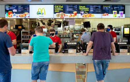 MINSK, BELARUS - June 11, 2020: Workers in medical masks serve customers at McDonald's restaurant during a Coronavirus epidemic. Lifestyle during pandemic. 新聞圖片