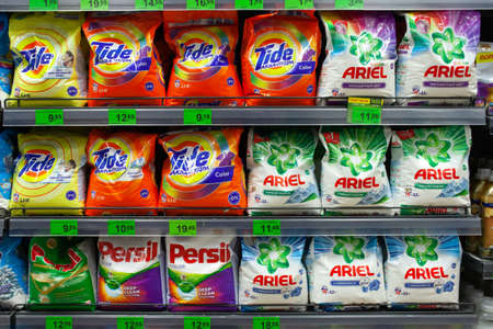 MINSK, BELARUS - July 4, 2020: Shelves in the store with different washing powder - Persil, Ariel, Tide