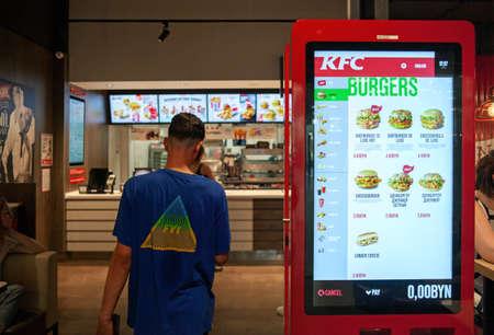 Minsk, Belarus, June 11, 2020: A kiosk for ordering food in KFC restaurant. A visitor enters a cafe. 新聞圖片