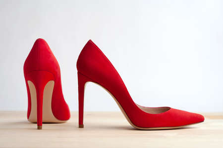 Red female shoes on a wooden floor.
