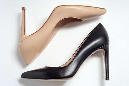 Beige and black stiletto heels on white